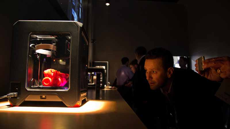 Trade show attendees examine the MakerBot Replicator Mini 3D printer at the International Consumer Electronics Show, Wednesday, Jan. 8, 2014, in Las Vegas. (AP Photo/Julie Jacobson)